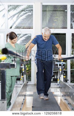 Female Physiotherapist Motivating Senior Man To Walk In Rehab Center