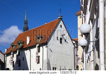 Tallinn building of the 17th century in the old city and flags with the coats of arms of the ancient cities of the Hanseatic union