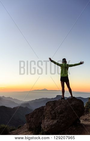 Woman successful hiking climbing silhouette in mountains motivation and inspiration in beautiful sunset and ocean. Female hiker with arms up outstretched on mountain top looking at night sunset inspirational landscape.