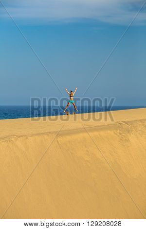 Woman with arms up outstretched on sand desert dunes running on beautiful inspirational desert dunes on sunny summer day. Female athlete runner jogging and exercising outdoors in nature Gran Canaria Canary Islands