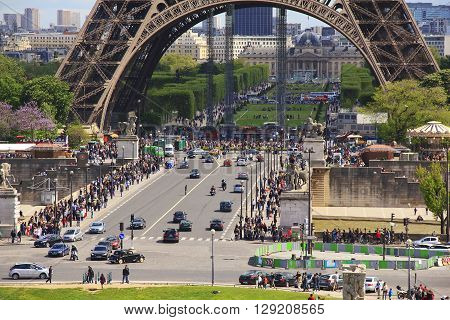 Paris, France - May 11: There are Ian Bridge Champ de Mars and the base of the Eiffel Tower filled to overflowing with tourists May 11, 2013 in Paris, France.