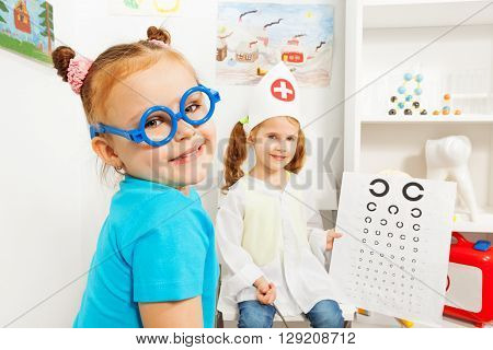 Cute little girl in blue toy glasses at the ophthalmologist room.