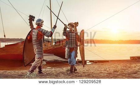 Battle Of Two Medieval Knights With Swords And Shields. Warships On The Background.