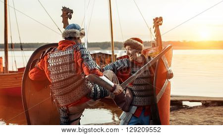 Battle Of Two Medieval Knights With Swords And Shields. Warship On The Background.