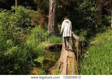 Person with red hair and a white coat hiking in the Olympic Peninsula in Washington State.