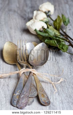 various spoons and forks on aged wooden background