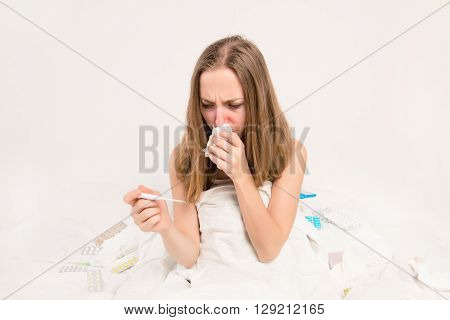 Portrait of ill woman with fever and running nose holding thermometer