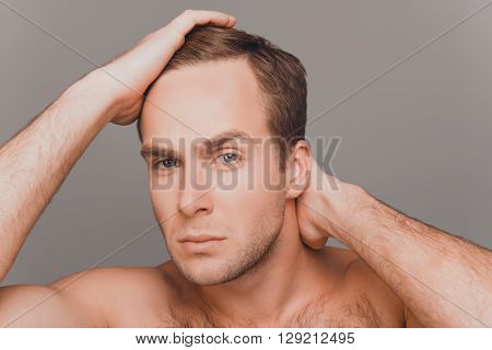 Portrait Of Young Man Combing His Hair With Fingers