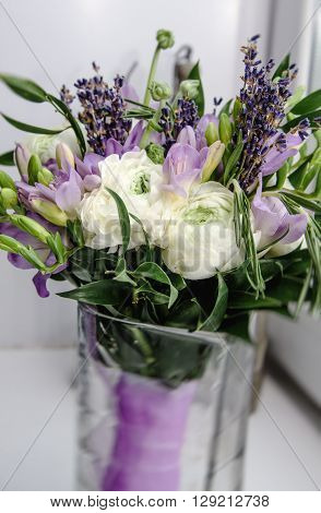 Beautiful rich bunch of purple fresia, white buttercup ranunculus peony, green leaf, lilac lavender, roses, rosemary bouquet flowers in vase with violet tape. White Background.