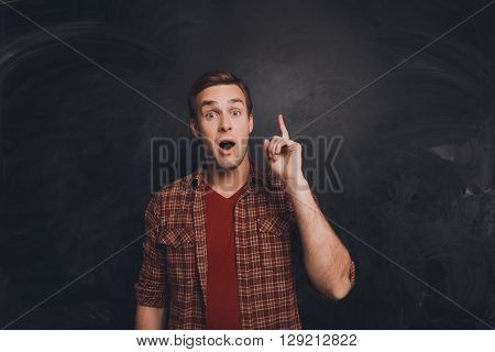 Smart Young Man With Raised Finger Having An Idea