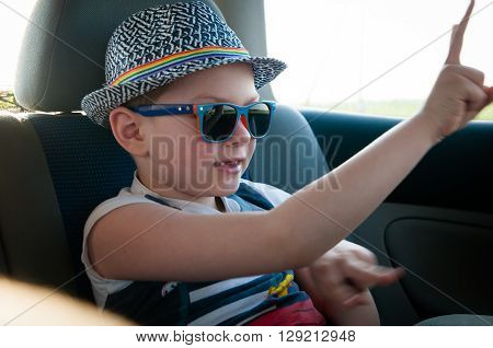 Boy rides in the car and hands dancing to the music