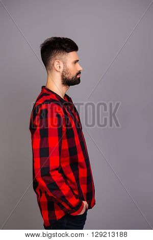 Side View Portrait Of Strict Brutal Man Holding Hands In Pockets