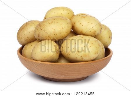 Raw unpeeled potatoes in a wooden bowl, isolated on white background.