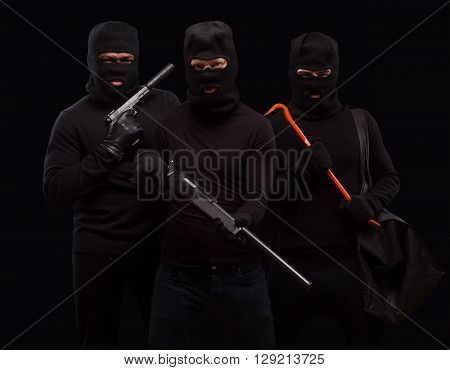 Robbers in black masks posing with rifles and crowbars over black background. Dangerous people going to do robbery or burglary. Isolated on black.