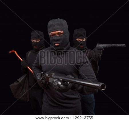 Closeup portrait of robber posing with rifle over black background with his partners. Studio shot of muscular men with weapons. Isolated on black.