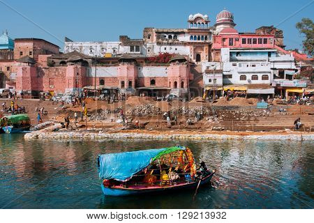 MADHYA PRADESH, INDIA - DEC 27, 2012: Beautiful indian city with old brick houses river ghat and blue color boat on water on December 27, 2012 in Chitracoot. Population of Chitrakoot is 22294 people.