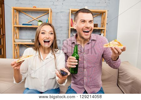Atractive Happy Young Man And Woman Watching Tv With Beer And Pizza