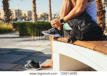 Man tying a shoelace and getting ready for fitness.