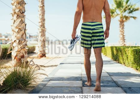 Man carrying slippers and going to the beach.
