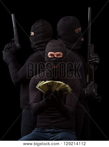Dangerous thieves posing in masks over black. Men in black balaclavas showing money stolen from house, apartment or flat in studio. Isolated on black.