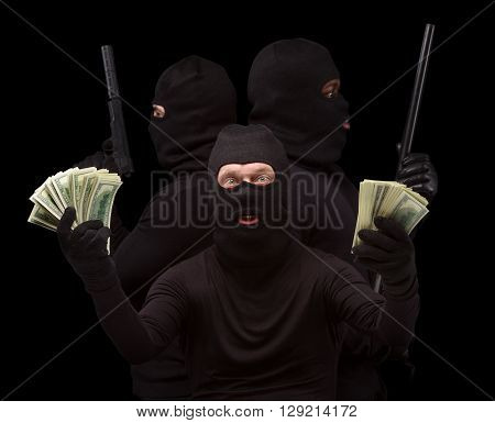 Closeup of dangerous thief showing much money. Men in black masks posing for photographer in studio over black background. Rifles, guns. Isolated on black.