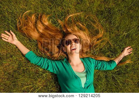 Happy Cheerful Long-haired Girl In Spectacles Lying On Lawn