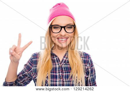 Portrait Of Hipster Smiling Girl In Cap And Glasses Showing Two Fingers