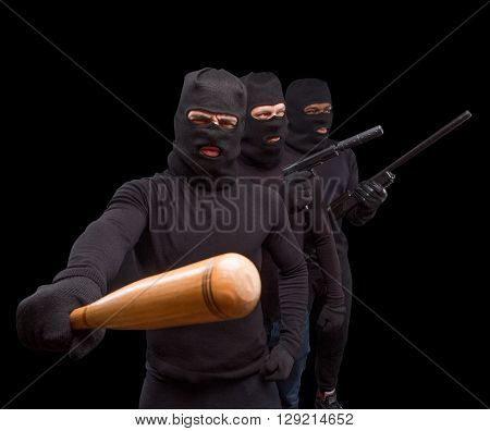 Masked men preparing to attack with bats, rifles and guns over black background. Men are going to sreal something or someone. Isolated on black.