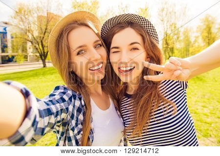 Two Pretty Girls Making Selfie, Gesturing With Two Fingers And Showing Tongue