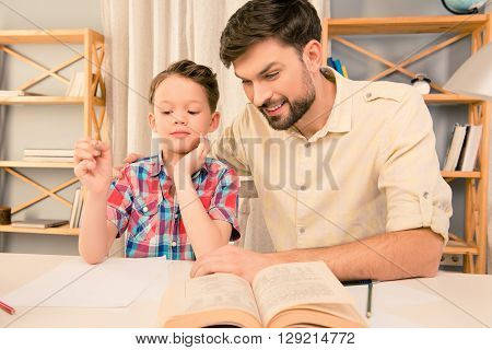 Father And Son Laughing While Reading Book At Home