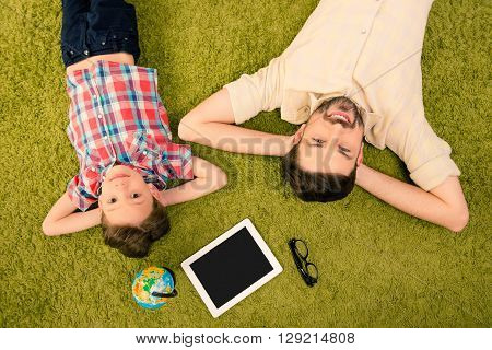 Father And Son Lying On Green Carpet With Globe, Tablet And Glasses