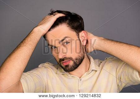 Portrait Of Handsome Bearded Man Combing Hair With Fingers