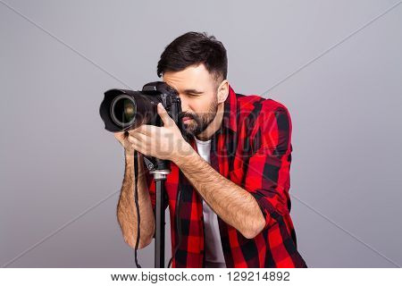 Portrait Of Male Photographer With  Professional Camera Isolated On Gray Background