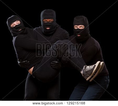 Picture of three handsome thieves or robberies in balaclavas over dark grey background. Dangerous man holding another man in arms. Isolated on black.