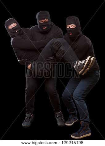 Portrait of three men in balaclavas and masks ready for robbery or burglary over dark grey background. Mafia and gangster concepts. Isolated on black.