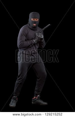 Male thief wearing mask and holding gun pointing up isolated on grey background. Handsome man in full length. Isolated on black. Isolated on black.