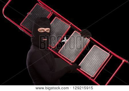 Portrait of masked thief posing with ladder over black background. Young man in balaclava going to rob house, apartment or flat. Isolated on black.