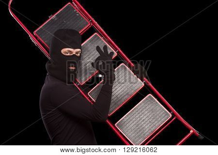 Masked thief carrying ladder and showing okay sign in studio. Dangerous robber going to steal something or someone from house, apartment or flat. Isolated on black.