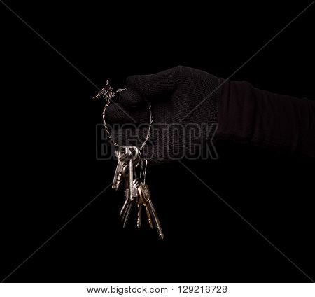 Keys from house, apartment or flat represented in thief's hand. Robber going to do robbery or stealing. Studio shot. Isolated on black.