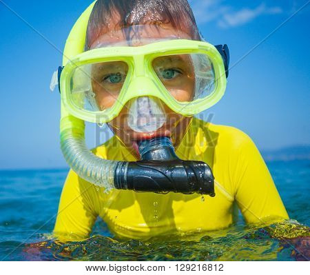 Portrait of joyful boy going to scuba diving in clear sea.
