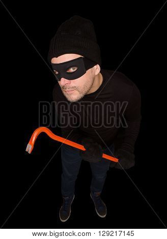 Funny masked robber or thief. View from top or from hidden camera. Handsome man holding crowbar over black background. Isolated on black.