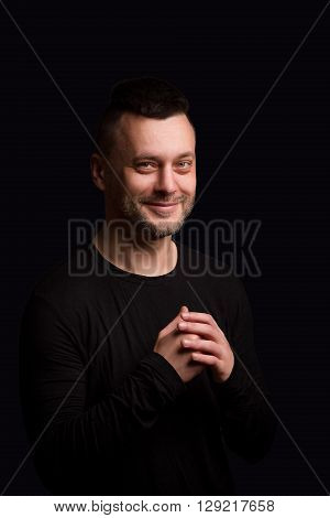Handsome man happy smiling for camera while having his hands clasped in front of him. Short-haired man in studio. Isolated on black.