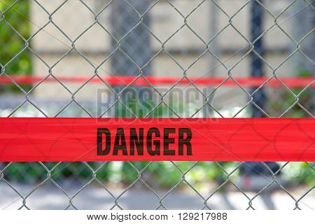 Red Reflective Danger Barrier Tape Across A Chain Link Fence