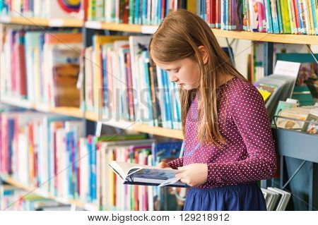 Little girl reading book in the library