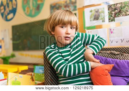 Indoor portrait of a cute little boy in a classroom