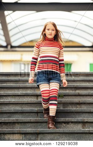 Fashion portrait of a cute little girl in a city, wearing brown boots, denim shorts, stripes rollnecck pullover and tights