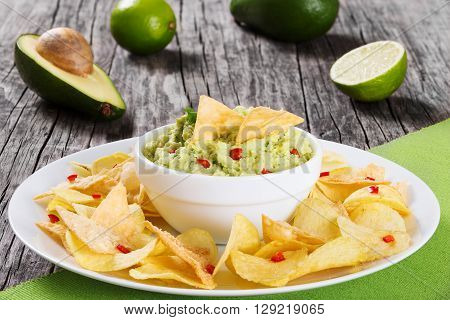 bowl of guacamole dip and potato chips on a dish on a wooden background view from above