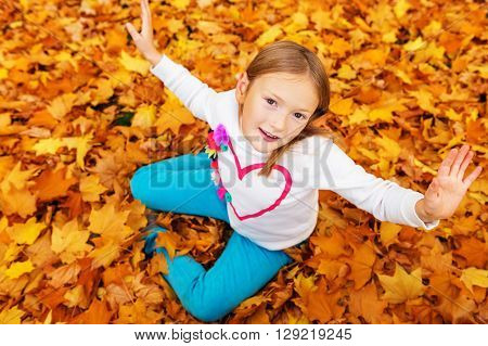Autumn portrait of a cute little girl of 8 years old, playing with yellow leaves in the park