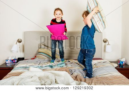 Two adorable kids having pillow fight on the bed
