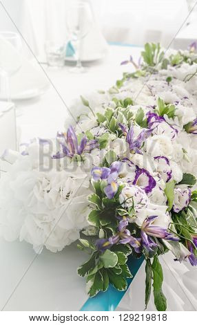 Luxury beautiful banquet table with rich decoration of flowers lush leaves white hydrangea cream roses purple eustoma blue iris in restaurant. Style summer sea wedding concept. Floral arrangement. Copy space text here